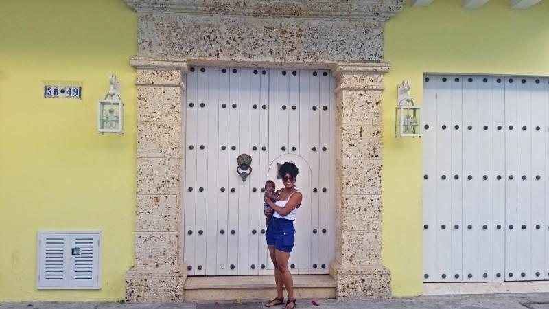mom holding baby in front of door