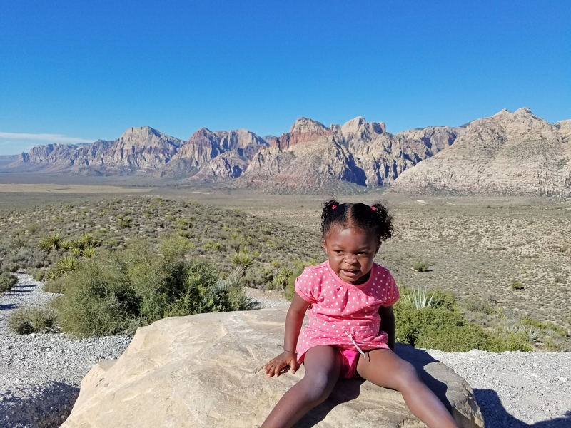 girl sitting on rock with red rock canyons in the background