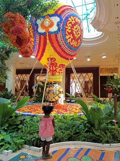 girl looking at a hot air balloon made out of flowers