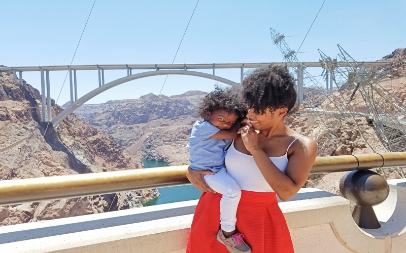 mom holding daughter in front of a bridge