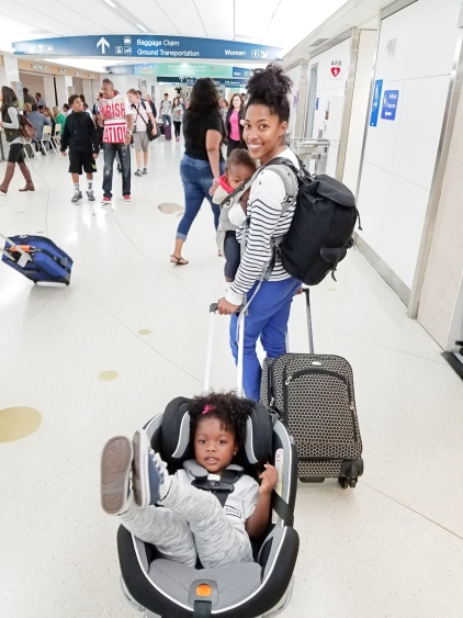 mother pulling a car seat with her child in the airport