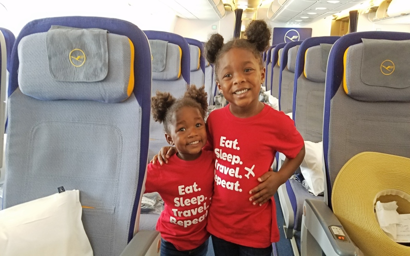 two toddler standing in the aisle on an airplane