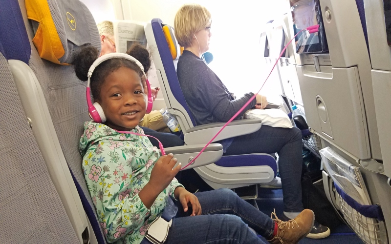 girl sitting on the plane with headphones on