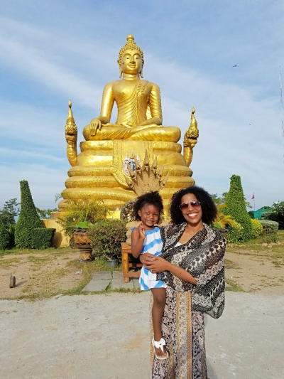 mom and daughter standing in front of a golden buddha in Thailand