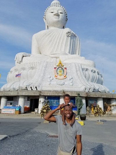 dad with child on his shoulders standing in front of a white huge buddha in Thailand