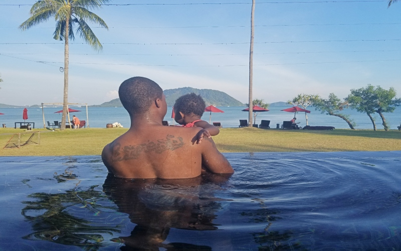 dad holding baby daughter in the pool