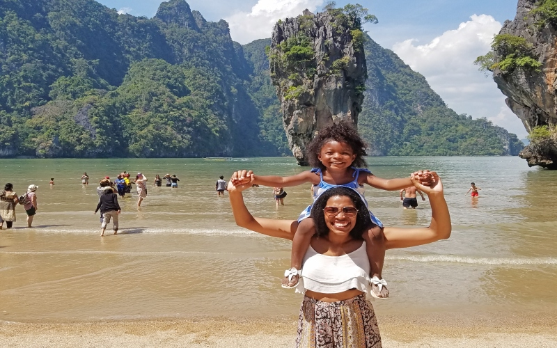 mom holding daughter on shoulders in front of rock formation spewing from the ocean