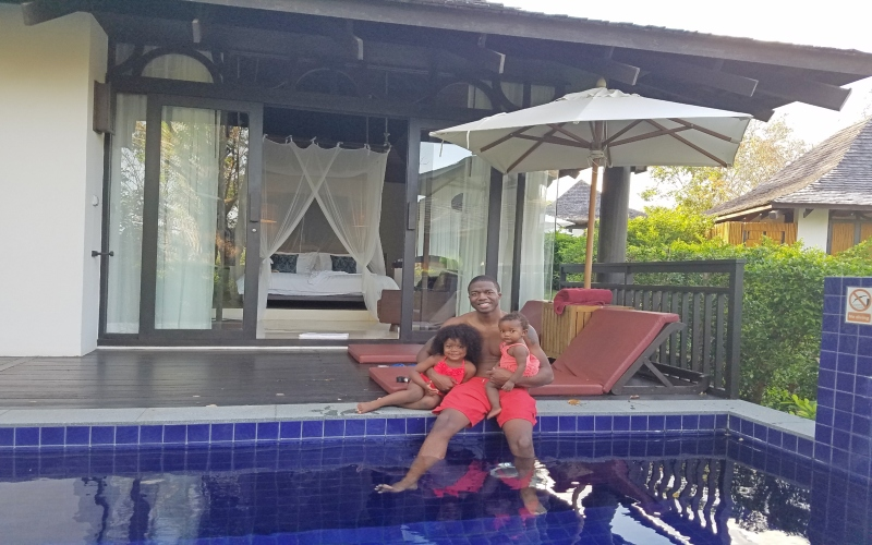 dad holding daughters on the side of the pool with hotel room in the background