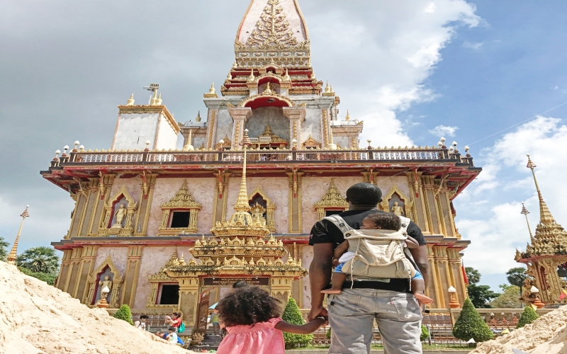 dad facing temple with baby on his back in a carrier and holding his daughters hand