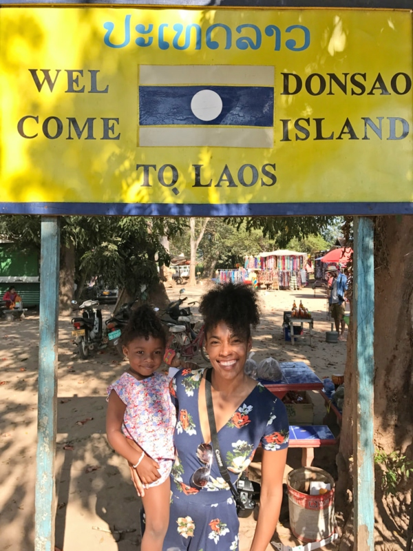 mom and daughter in front of welcome to Laos sign