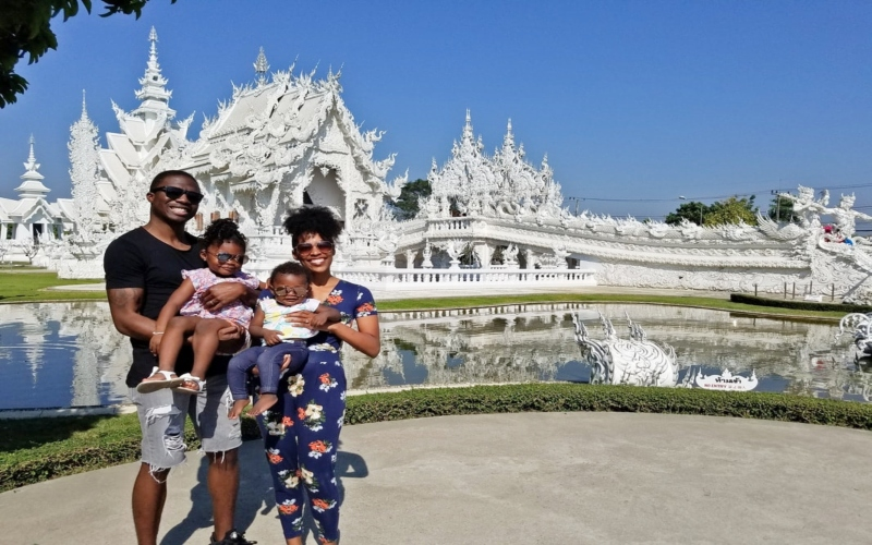 family in front of a white temple in thailand