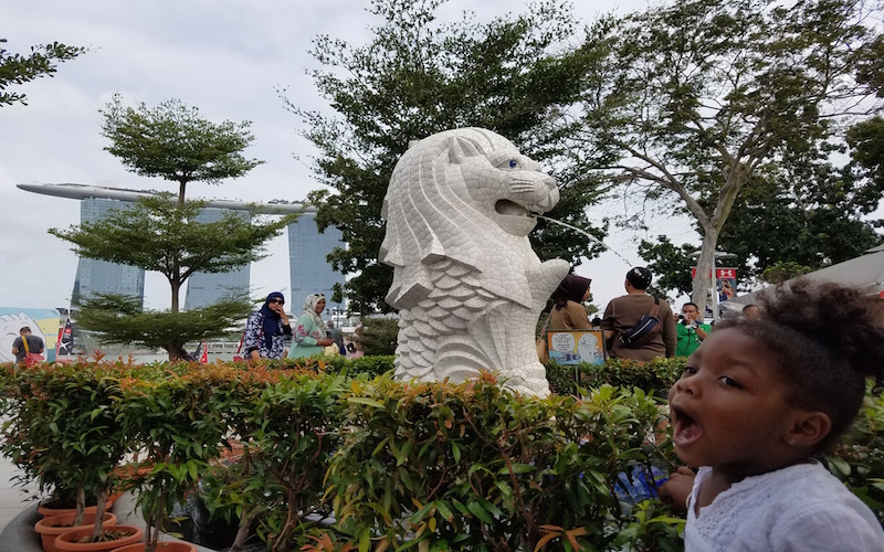 Toddler pretending to catch the water sprouting from a lion statue in Merlion Park