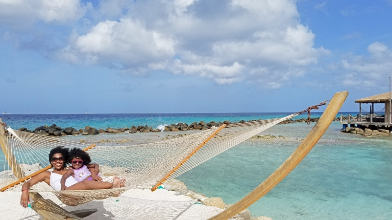 mom and daughter laying on a hammock by the beach