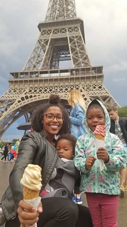 mom and daughters eating ice cream in front of the Eiffel Tower