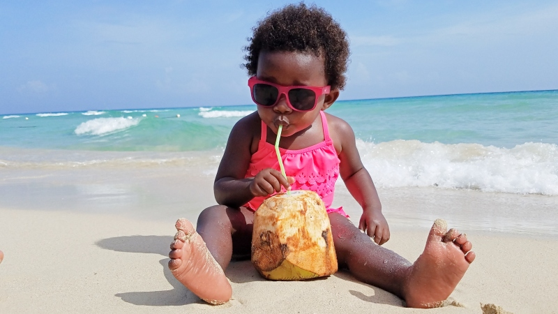 toddler on the beach drinking from a coconut