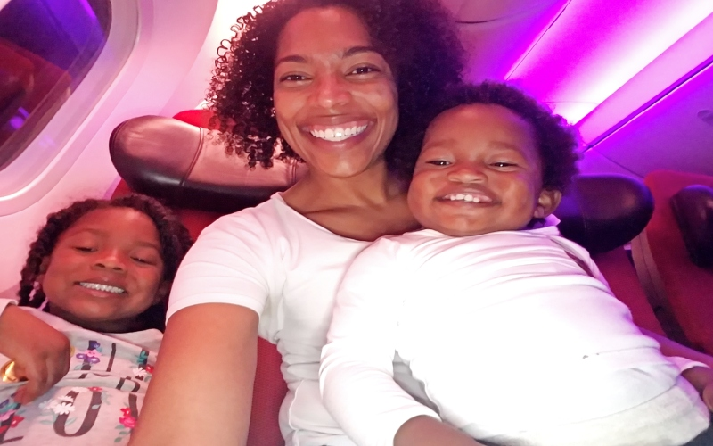mom and daughters sitting on a plane
