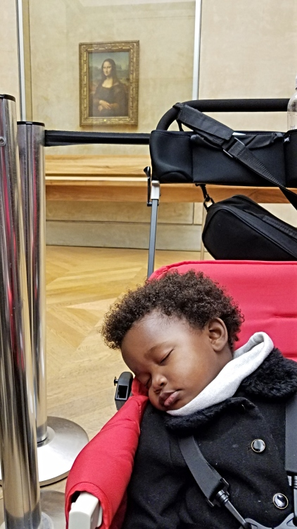 baby sleeping in stroller in front of the Mona Lisa