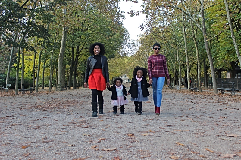 Two ladies walking down a treed path holding hand with two girl toddlers