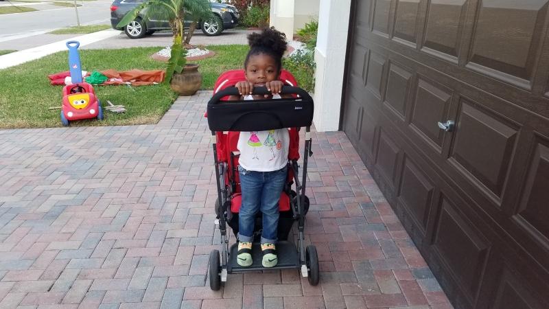 girl standing on stroller