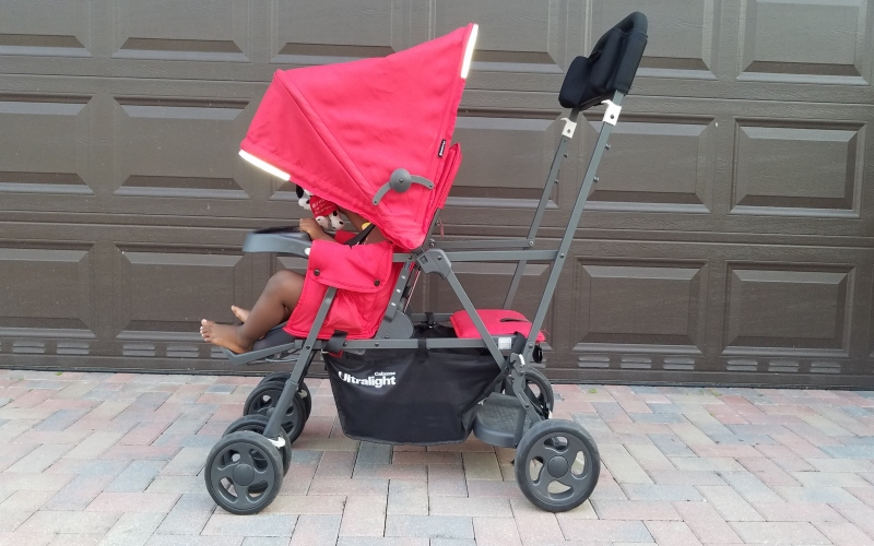 red stroller with toddler in it