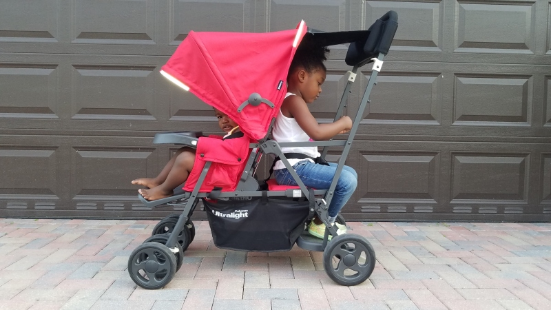 two kids in a red double stroller