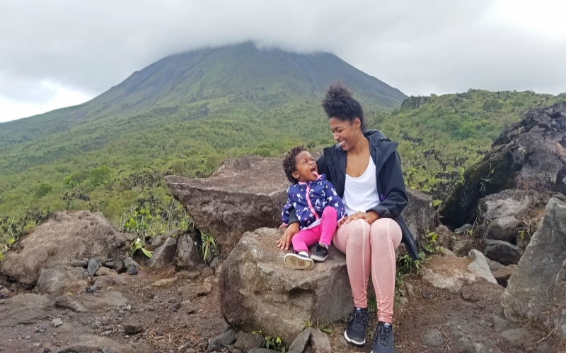 mom and daughter sitting on rock with arenal volcano in the background