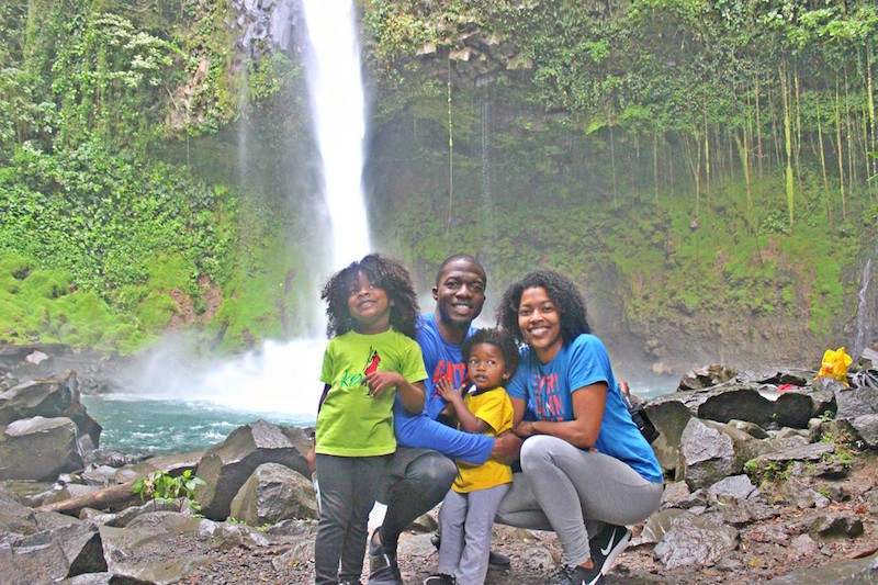 family kneeling in front of waterfall
