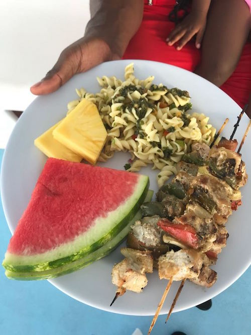 plate of food with watermelon, pineapple, pasta, chicken stewers