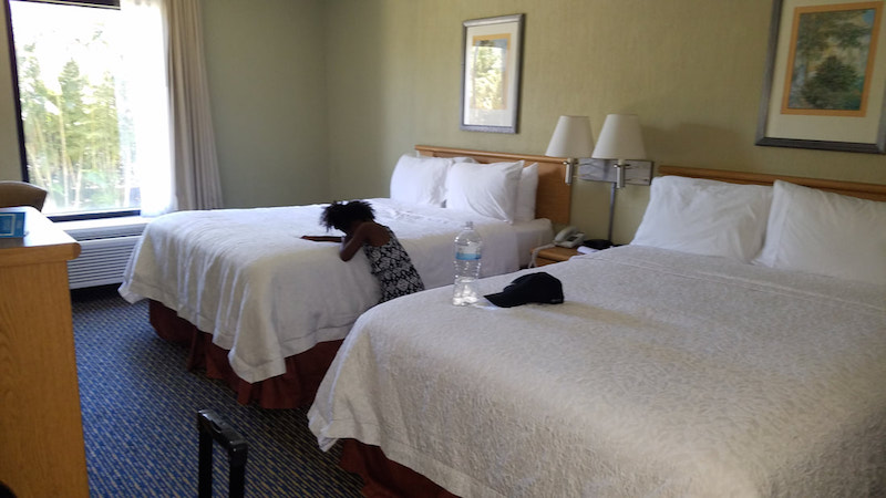 little girl laying on bed in hotel room