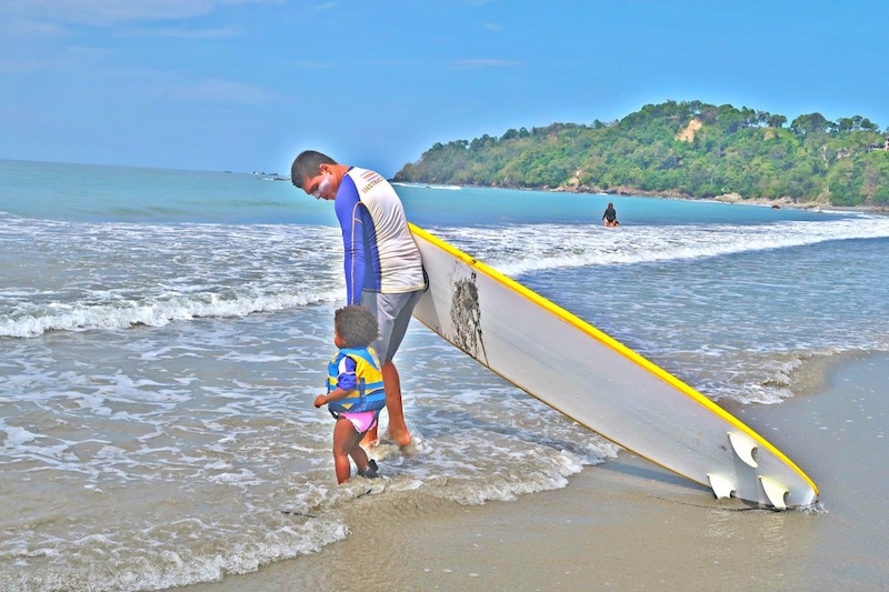 toddler holding her surf instructors hand while walking into the ocean