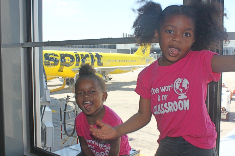 two toddler standing at the window of the airport with a spirit airlines plane in the background