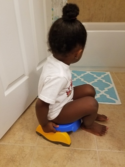 little girl sitting on a potty