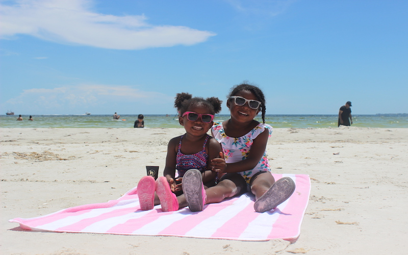 Two toddler sisters sitting on a pink and white towel at the beach