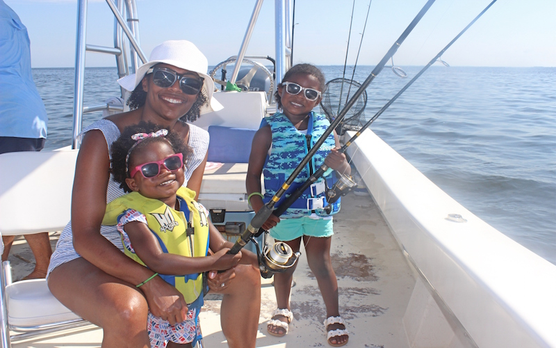 two kids and mom fishing on a boat