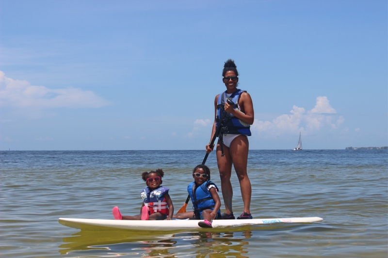 Mom standing up on paddle board with two young daughters sitting down in the ocean