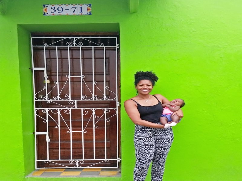woman holding child in front of a green house