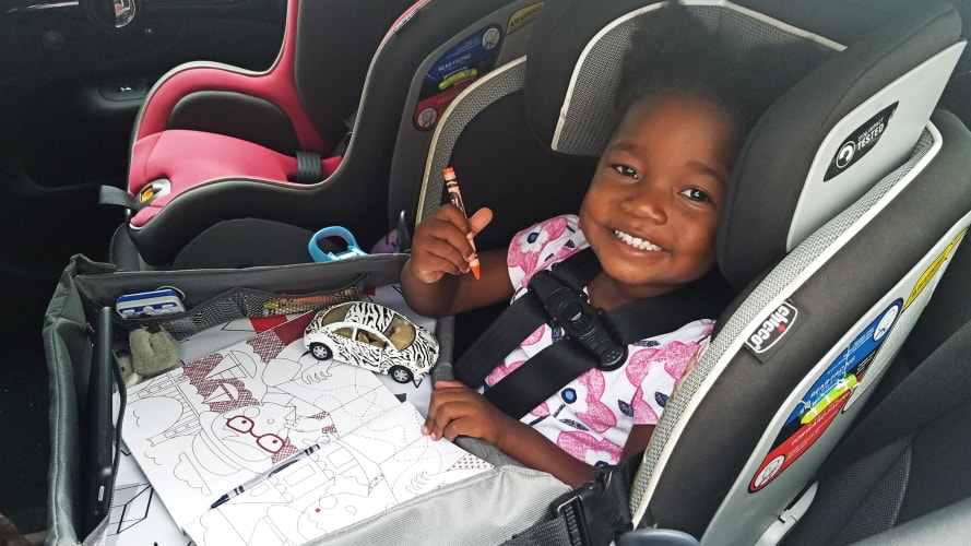 little girl coloring in car seat