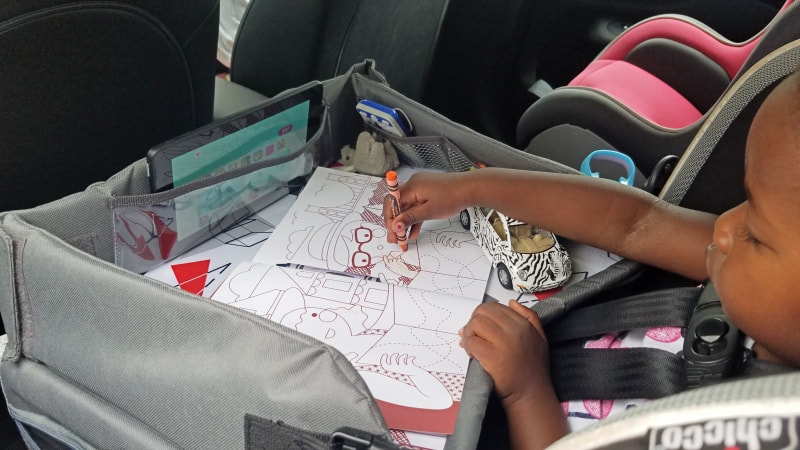 little girl coloring in the car