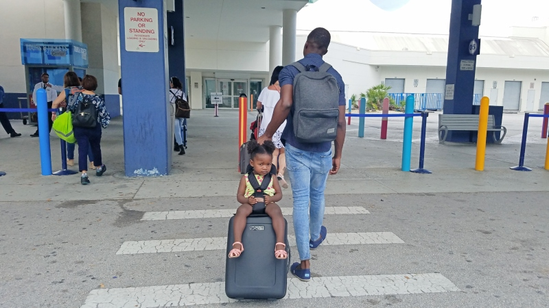 dad pulling suitcase with toddler sitting on top of it