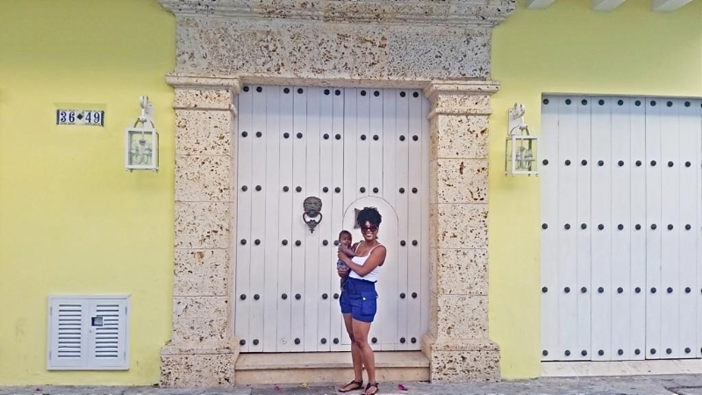 mom holding newborn in front of pretty door