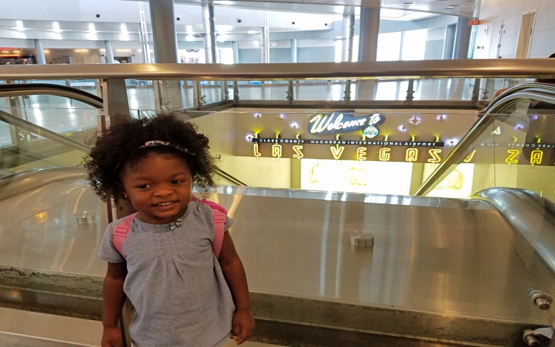 Toddler girl standing in front of the welcome to Las Vegas sign at the airport