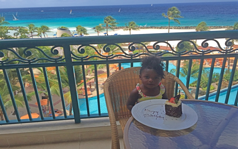 toddler girl eating birthday cake on the balcony with pool and beach in the background