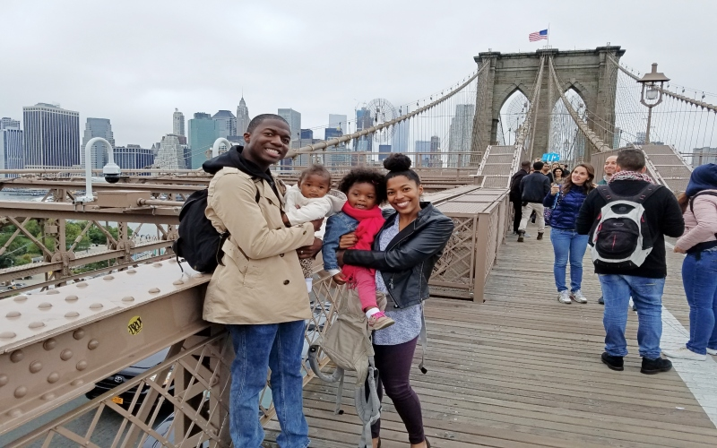 family standing in front of the Brooklyn Bridge