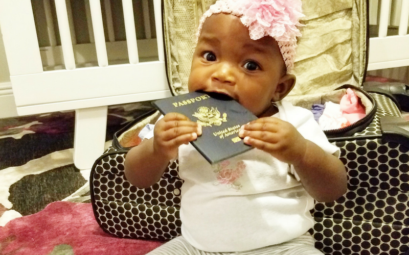 baby sitting on the floor in front of a suitcase eating her passport