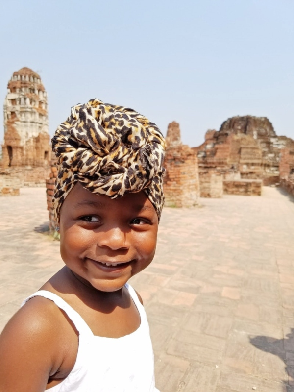 toddler girl in leopard head wrap in front of temple in ayutthaya thailand