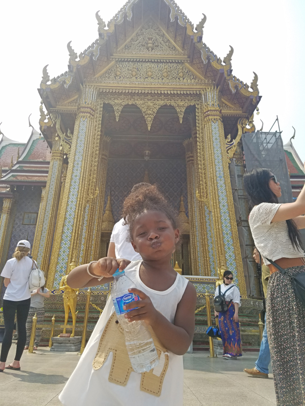 toddler girl standing in front of a palace in Thailand