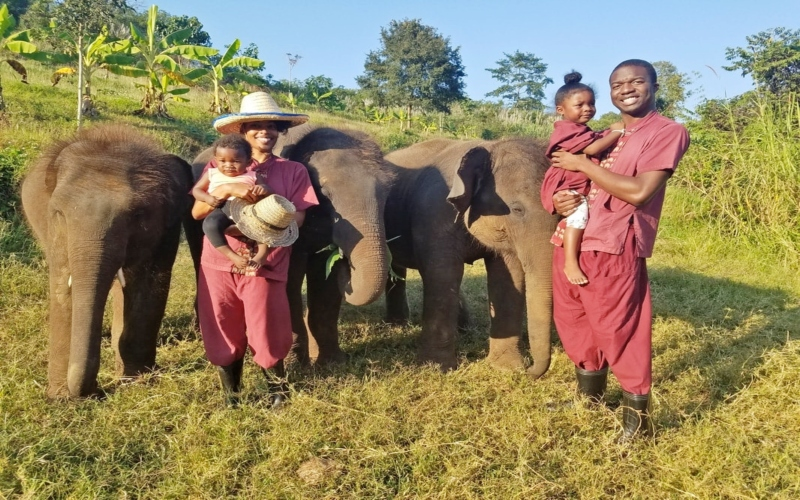 family posing with elephants at a sanctuary