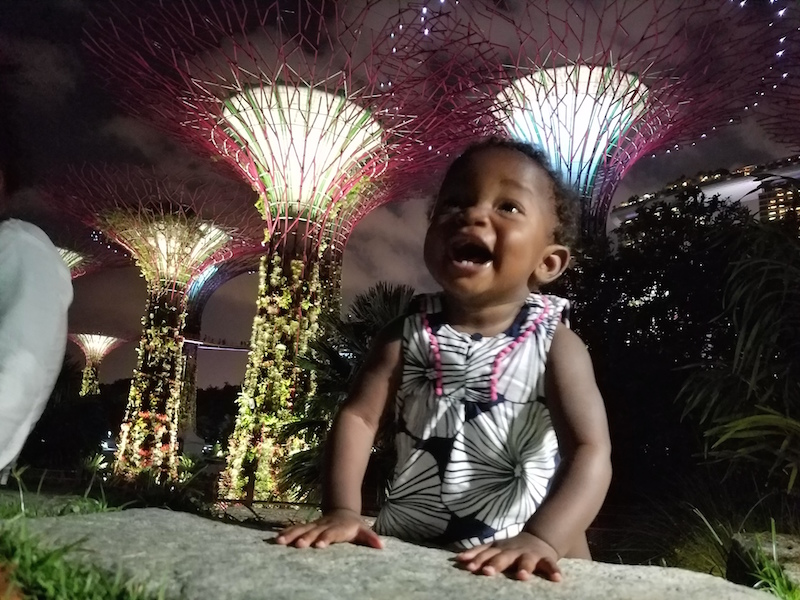 Infant sitting up in amazement of with lit up trees in the background