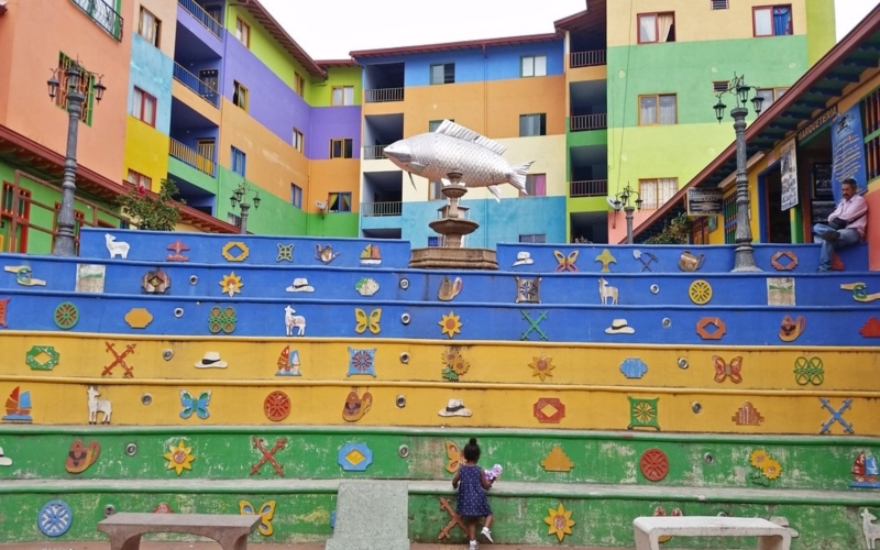 toddler girl climbing up a colorful staircase