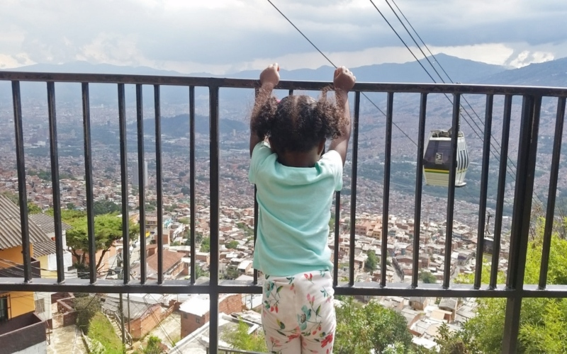 girl standing holding onto railing over looking mountain and cable car